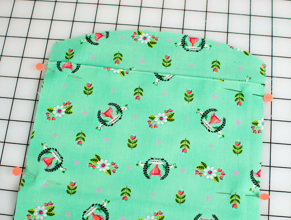 Make a pleat by placing the topstitched edge about 1'' below the closest curved edge. Pin the sides.